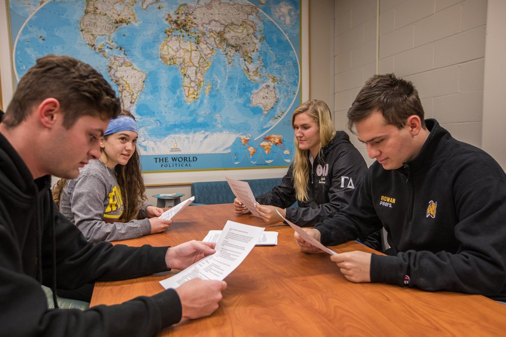 four students sitting at a table with a world map behind them