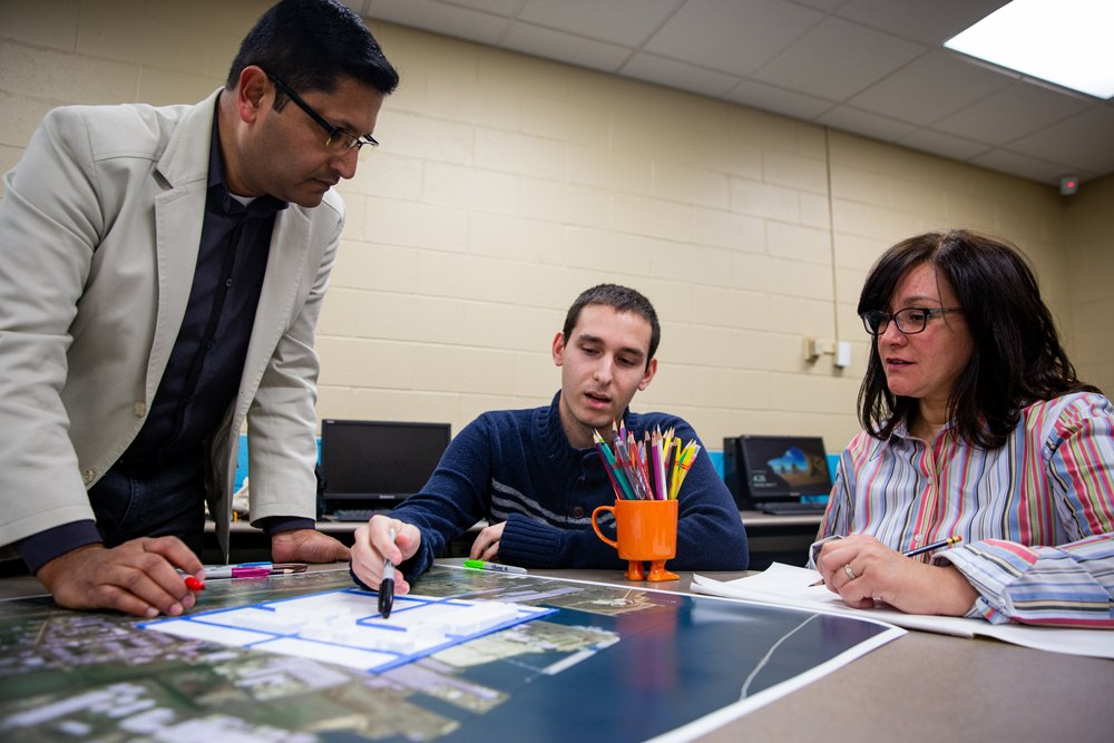 Two students and a professor working on a map together