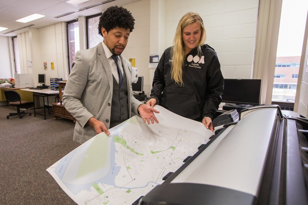 A student and a professor working on a printed map